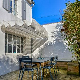 Foto de terraza marinera, de tamaño medio, en patio trasero, con toldo