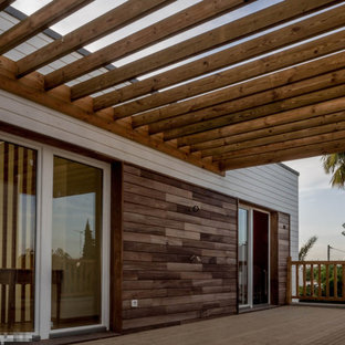 Danish deck photo in Toulouse with a fire pit and a pergola
