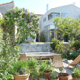 This is an example of a mediterranean backyard deck in Other with a container garden and no cover.