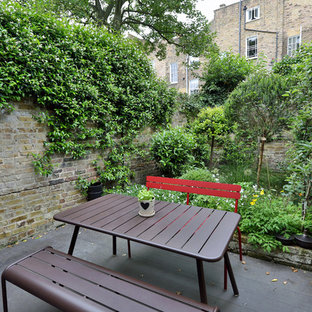 This is an example of a medium sized urban back terrace in Paris with a potted garden and no cover.
