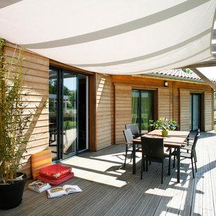 Inspiration pour une terrasse avec des plantes en pots arrière chalet de taille moyenne avec une pergola.