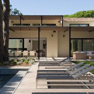 Idée de décoration pour une grande terrasse arrière design.