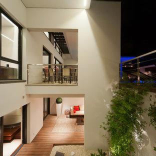 Inspiration pour une grande terrasse arrière design avec une terrasse en bois et une extension de toiture.