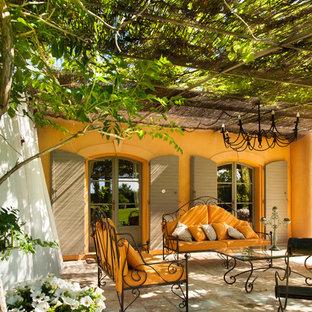Diseño de patio mediterráneo, en patio delantero, con adoquines de piedra natural y pérgola