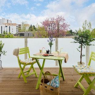 Esempio di una terrazza country con un giardino in vaso, nessuna copertura e parapetto in vetro