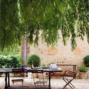 Aménagement d'une terrasse avec des plantes en pots arrière campagne avec du gravier et aucune couverture.