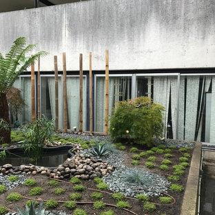 Foto di un grande patio o portico etnico dietro casa con fontane, ghiaia e nessuna copertura