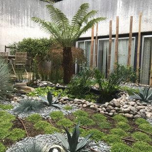 Idee per un grande patio o portico etnico dietro casa con fontane, ghiaia e nessuna copertura