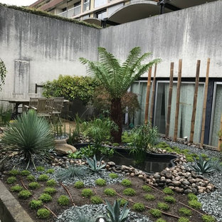 Immagine di un grande patio o portico etnico dietro casa con fontane, ghiaia e nessuna copertura