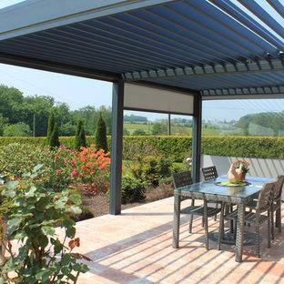 Cette photo montre une terrasse tendance de taille moyenne avec du carrelage et une pergola.