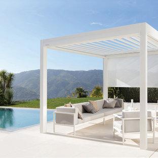 Idées déco pour une grande terrasse contemporaine avec du carrelage et une pergola.