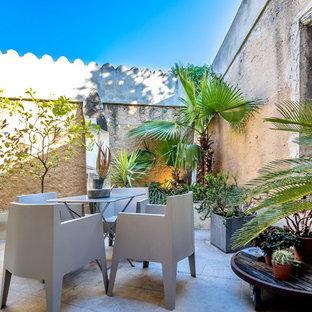 Inspiration pour une terrasse avec des plantes en pots méditerranéenne de taille moyenne avec des pavés en pierre naturelle et aucune couverture.