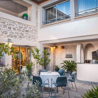 Cette photo montre une terrasse avec une cuisine extérieure méditerranéenne de taille moyenne avec une cour, des pavés en pierre naturelle et aucune couverture.