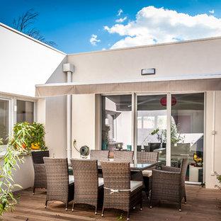 Idée de décoration pour une terrasse avec des plantes en pots arrière design de taille moyenne avec un auvent.