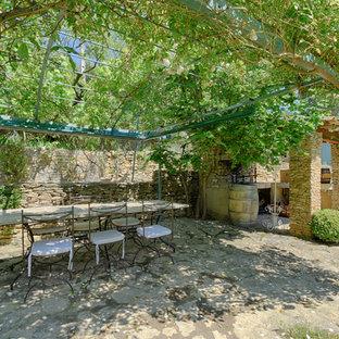 Exemple d'une terrasse arrière méditerranéenne avec des pavés en pierre naturelle et une pergola.