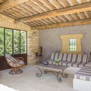 Inspiration pour une terrasse méditerranéenne de taille moyenne avec une extension de toiture, des pavés en pierre naturelle et une cheminée.