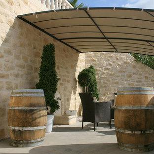 Idées déco pour une terrasse avec des plantes en pots méditerranéenne avec une dalle de béton et un auvent.