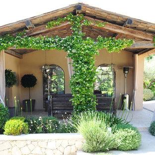 Exemple d'un mur végétal de terrasse arrière méditerranéen de taille moyenne avec des pavés en pierre naturelle et une extension de toiture.