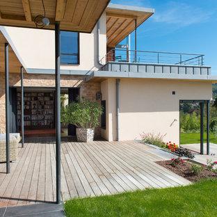 Cette image montre une grande terrasse avec des plantes en pots arrière design avec un auvent.