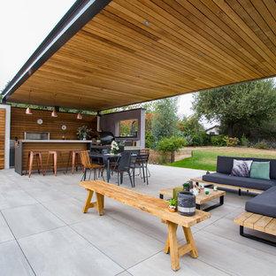 Cette photo montre une terrasse avec une cuisine extérieure arrière tendance de taille moyenne avec du carrelage et une pergola.