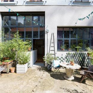 Idées déco pour une terrasse avec des plantes en pots industrielle avec une dalle de béton et aucune couverture.
