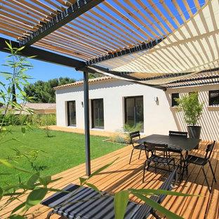 Exemple d'une terrasse avec des plantes en pots arrière tendance de taille moyenne avec une pergola.