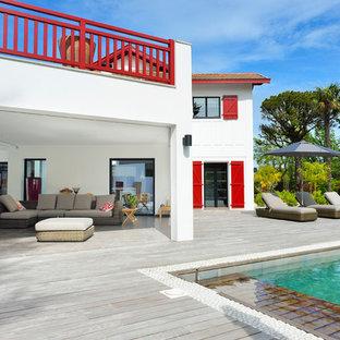 Inspiration pour une grande terrasse arrière design avec une extension de toiture et un foyer extérieur.