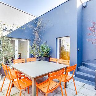 Exemple d'une terrasse avec des plantes en pots tendance de taille moyenne avec une cour, du carrelage et aucune couverture.