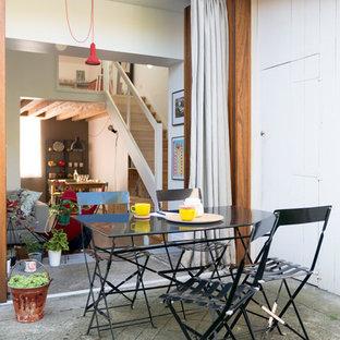 Aménagement d'une terrasse arrière scandinave avec une dalle de béton et aucune couverture.