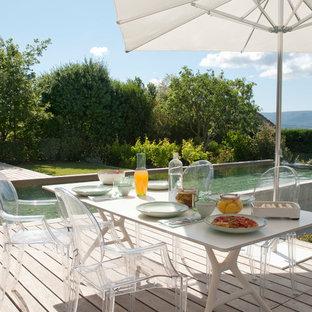 Cette image montre une terrasse arrière design de taille moyenne avec une terrasse en bois et aucune couverture.