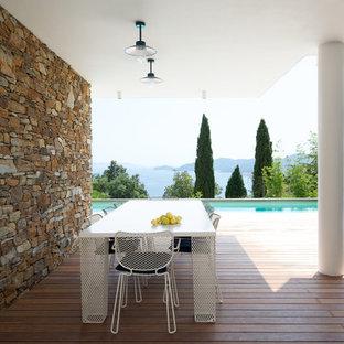 Cette image montre une grande terrasse arrière design avec une extension de toiture.