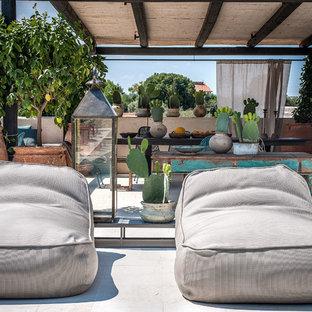 Esempio di un patio o portico mediterraneo con un giardino in vaso e una pergola
