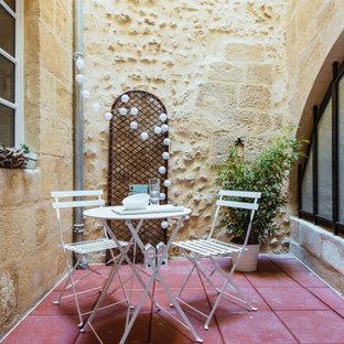 Idee per un piccolo patio o portico shabby-chic style dietro casa con piastrelle