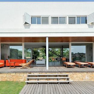 Exemple d'une grande terrasse et balcon arrière méditerranéenne avec une extension de toiture.