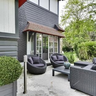 Inspiration pour une terrasse avec des plantes en pots arrière traditionnelle de taille moyenne avec aucune couverture et une dalle de béton.
