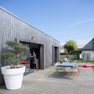 This is an example of a mid-sized contemporary backyard deck in Nantes with no cover and a container garden.