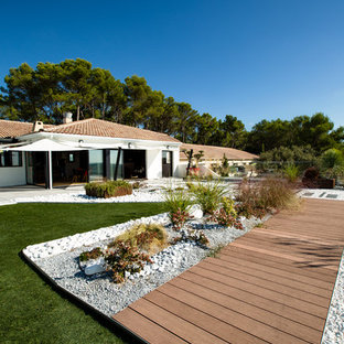 Photo of a large contemporary patio in Montpellier with gravel, an awning and a potted garden.