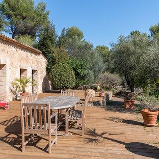 Idée de décoration pour une terrasse avec des plantes en pots arrière méditerranéenne avec aucune couverture.