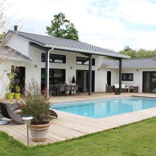 Cette image montre une terrasse arrière design avec une extension de toiture.