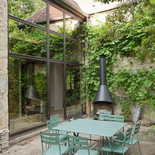Aménagement d'une petite terrasse campagne avec aucune couverture, une cour, une dalle de béton et une cheminée.