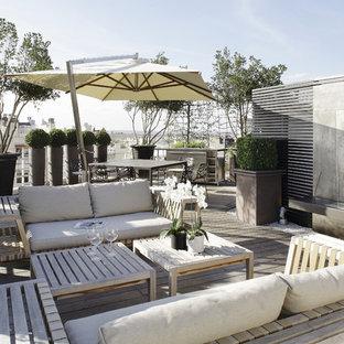 Idée de décoration pour une terrasse design avec un foyer extérieur.