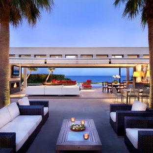 Idée de décoration pour une grande terrasse latérale design avec des pavés en béton et aucune couverture.