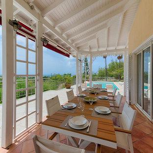 Idées déco pour une terrasse arrière méditerranéenne avec du carrelage et une extension de toiture.