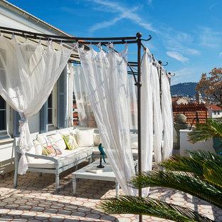 Idée de décoration pour une terrasse latérale méditerranéenne avec une pergola.
