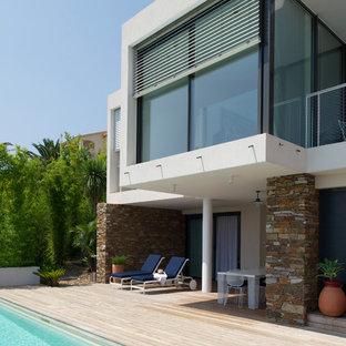 Réalisation d'une terrasse arrière design de taille moyenne avec une extension de toiture.