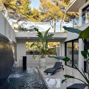 Exemple d'une grande terrasse exotique avec un point d'eau, une cour, du carrelage et aucune couverture.