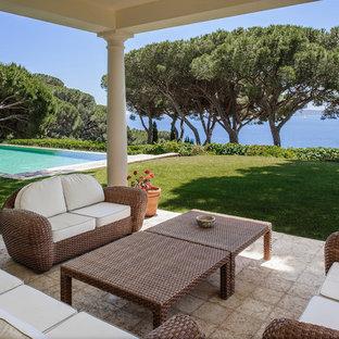 Exemple d'une terrasse avec des plantes en pots arrière chic de taille moyenne avec une extension de toiture et des pavés en pierre naturelle.