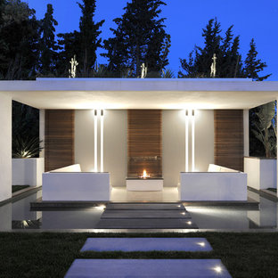 Cette image montre une terrasse arrière design de taille moyenne avec un gazebo ou pavillon et un foyer extérieur.