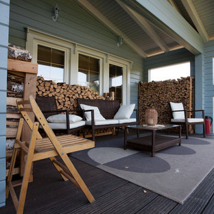 Example of a mid-sized danish backyard deck design in Moscow with a roof extension