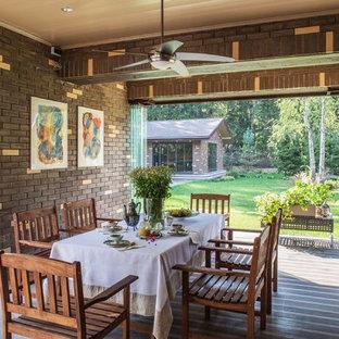 Cette image montre une grand véranda design avec sol en stratifié, une cheminée standard, un manteau de cheminée en brique, un plafond standard et un sol marron.